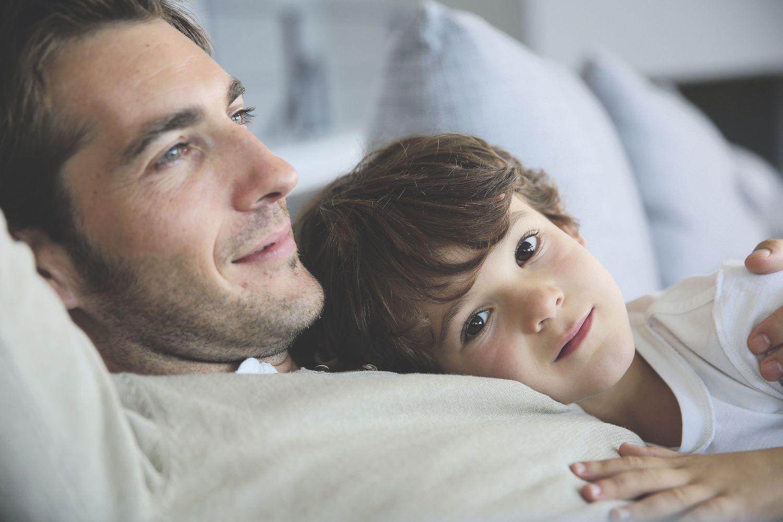 Vater entspannt mit seinem Sohn im Liegen. Thema: Komfort im Zug