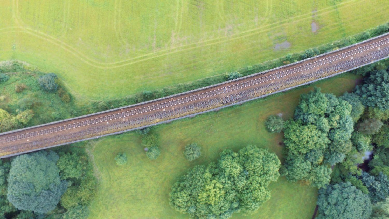 Bahngleise, die durchs Grüne führen. Thema: Ökostrom