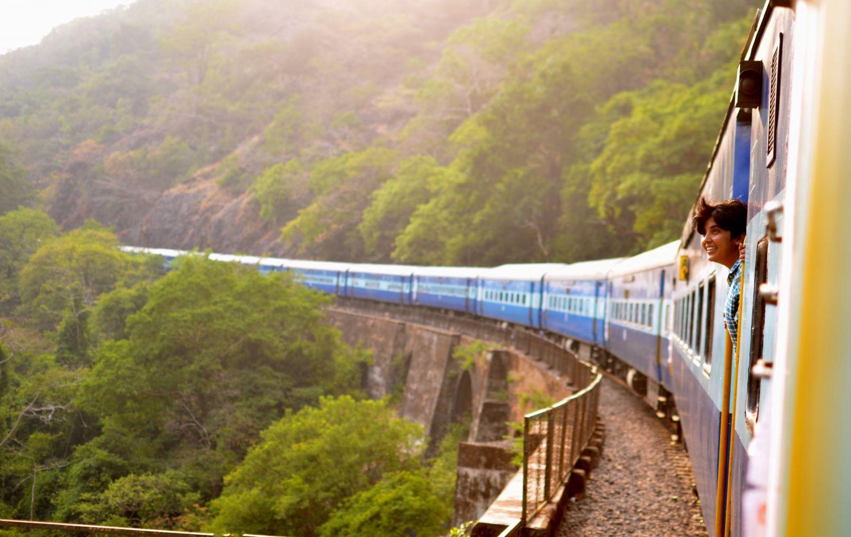 Eine Person schaut aus einer durch Gebirge fahrenden Eisenbahn heraus.
